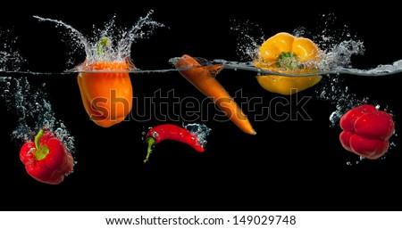 Fresh vegetables splashing in water on black background - stock photo