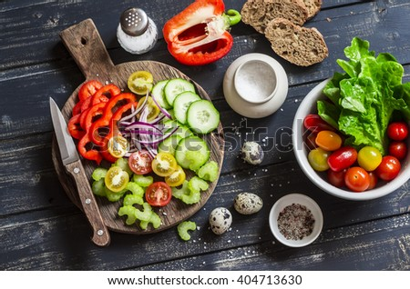 Fresh vegetables - tomatoes, cucumbers, peppers, celery and garden herbs and spices on dark wooden background. Ingredients for fresh vegetable salad - stock photo