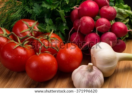 Fresh vegetables, tomatoes, twig tomatoes, radishes, bunch of radishes, garlic, clove garlic, herbs, parsley, fennel, healthy food, healthy eating, on a wooden board