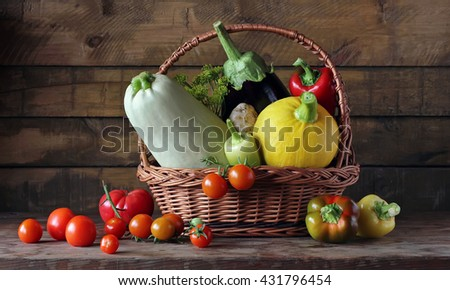 Fresh vegetables: tomatoes, zucchini, peppers, squash, eggplant, garlic in the basket on the table from the boards. Still life with vegetables in rural style. - stock photo