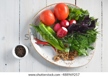 fresh vegetables, walnuts and pepper on a plate on white wooden background