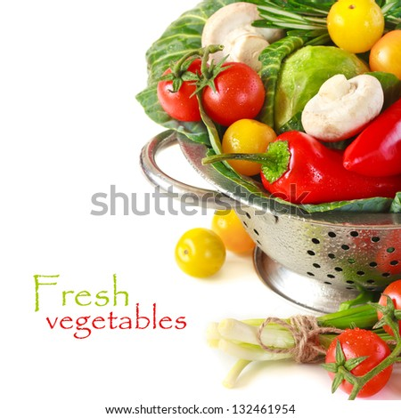 Fresh vegetables with water drops in a colander on a white. - stock photo