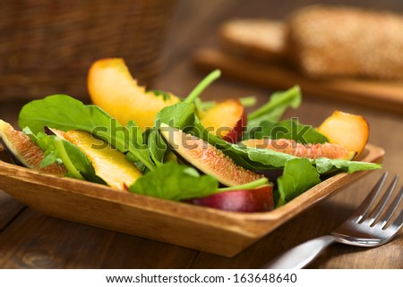 Fresh vegetarian salad made of fig, nectarine, spinach, cucumber and lettuce on wooden plate with wholewheat bread in the back (Selective Focus, Focus on the fig slice in the front)    - stock photo