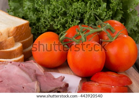 Fresh vine tomatoes with roast beef, bread and lettuce