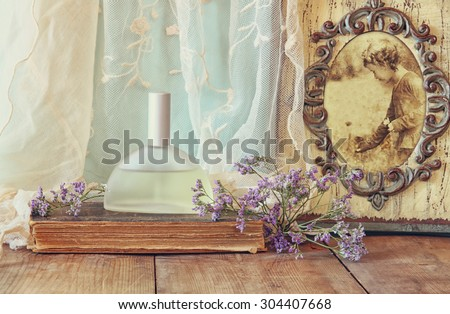 fresh vintage perfume bottle next to aromatic flowers and antique frame with old photography on wooden table. retro filtered image - stock photo