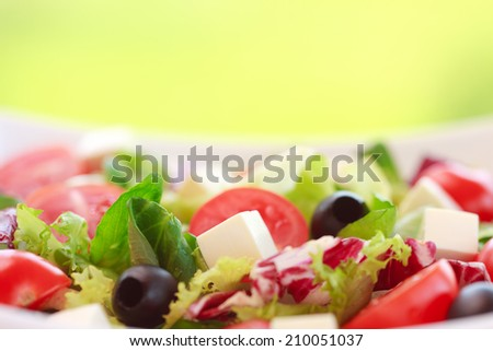 Fresh vitamin salad with tomatoes, feta cheese, olive, spinach,arugula, and lettuce