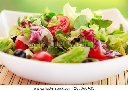 Fresh vitamin salad with tomatoes, olive, spinach,arugula, and lettuce