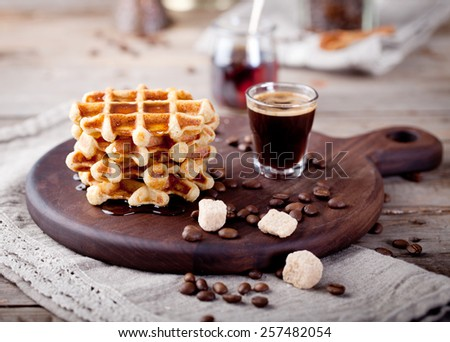 Fresh waffles with maple syrup and coffee on a wooden background.  - stock photo