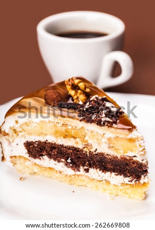 fresh walnut cake and cup of coffee on a brown background