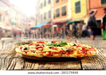 fresh warm pizza and table on street in italy  - stock photo