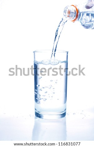 Fresh water pouring in a glass on white background.