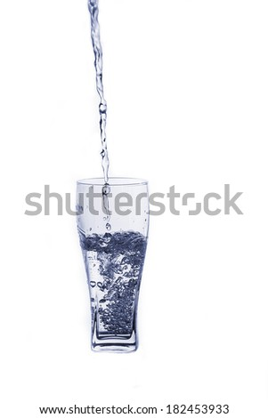 Fresh water pouring in a glass on white background
