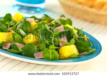 Fresh watercress, pineapple and ham salad on blue plate with bread ...