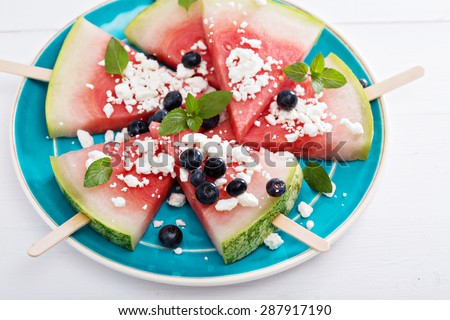 Fresh watermelon popsicles with blueberries and cheese cut on ice - stock photo