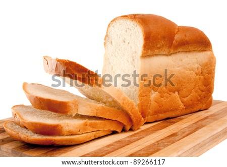 fresh wheat sliced bread on kichen board over white - stock photo
