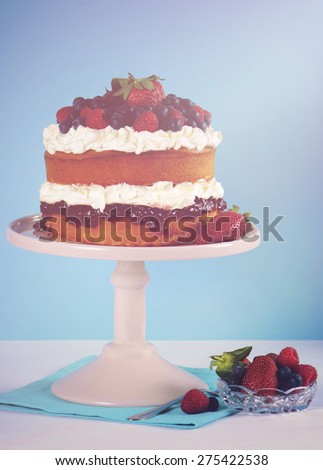 Fresh whipped cream and berries layer sponge cake on pink cake stand against pale blue and white background, with applied retro style filters and added lens flare light beam. - stock photo