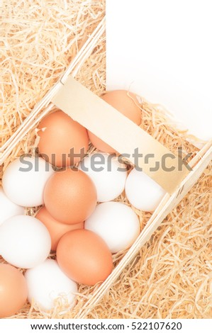 Fresh white and brown chicken eggs in chip basket with wood wool and white sign; Organic hen's eggs from the producer; Egg production