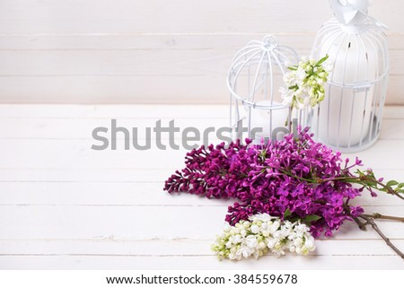 Fresh white and violet lilac flowers and candles on white painted wooden planks. Selective focus. Place for text.  - stock photo