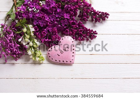 Fresh white and violet lilac flowers and decorative pink heart  on white painted wooden planks. Selective focus. Place for text. - stock photo