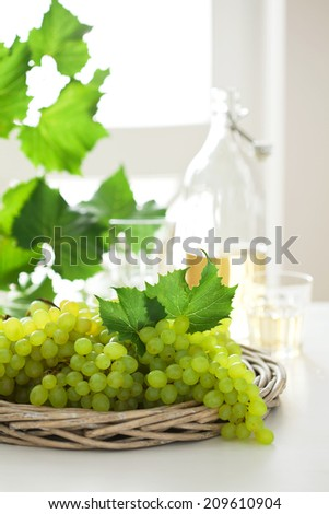 Fresh white grapes in basket and wine on the table, selective focus - stock photo