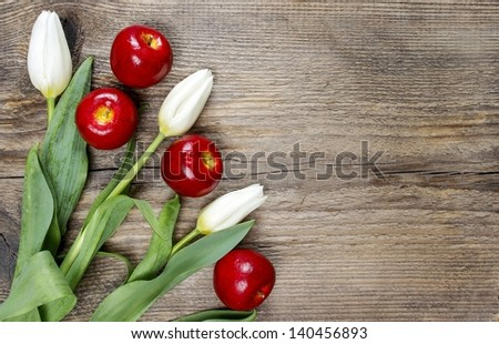 Fresh white tulips and stunning red apples on wooden background