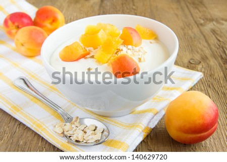 Fresh white yogurt in bowl with apricots and cereal (flakes, granola) over rustic wooden background (table). Healthy breakfast, copy space. - stock photo