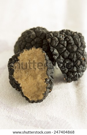Fresh whole and cut black Perigord truffles, Tuber melanosporum, a gourmet aromatic subterranean edible fungus found in the Perigord region of France - stock photo