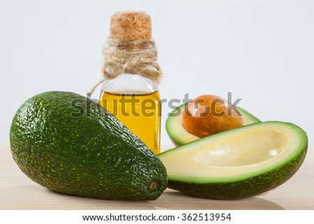 Fresh whole and sliced avocado and a bottle of oil on wooden table- spa, bodycare and haircare concept - stock photo