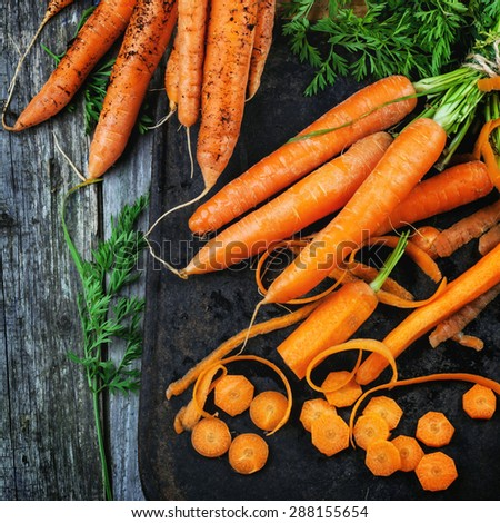 Fresh whole and sliced carrots over black cutting board over wooden table. Top view. Square image.  - stock photo