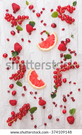 Fresh whole and sliced red fruits. Collection of fresh whole and sliced red fruits on white rustic background. Still life pattern background. Overhead view - stock photo
