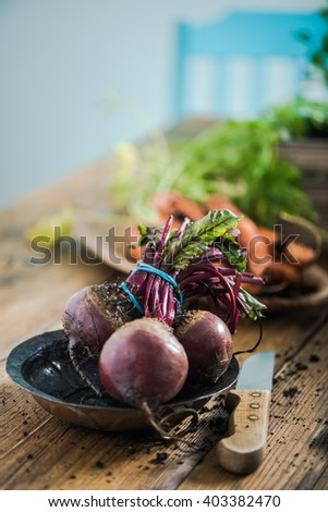 Fresh whole beetroot from garden soil, on wooden farmhouse table in kitchen - stock photo
