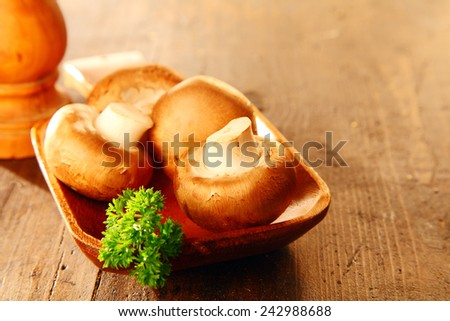 Fresh whole brown button mushrooms, Agaricus bisprous, and parsley on a wooden dish with a pepper mill with copyspace - stock photo