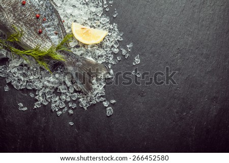 Fresh whole fish cooling on crushed ice garnished with herbs and lemon, tail view diagonally from a corner over a slate background with copyspace - stock photo