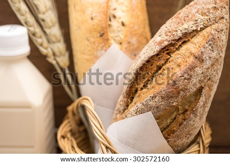 Fresh whole grain wheat bread loaf in bamboo basket with bottle of milk for healthy breakfast background - stock photo