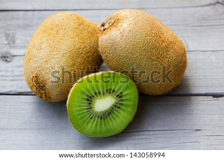 Fresh Whole kiwi fruit and his sliced half on wooden background - stock photo