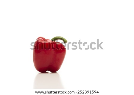 Fresh whole red bell pepper or capsicum on a white background with reflection viewed from the side with copyspace - stock photo