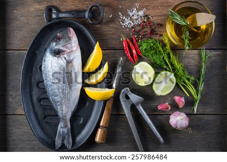 Fresh whole sea fish on iron rustic pan,cooking concept - stock photo