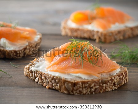 Fresh whole wheat sandwiches with smoked salmon on a wooden table - stock photo