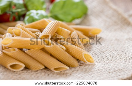 Fresh wholemeal Penne on an old wooden table - stock photo