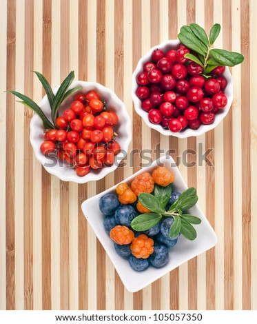 fresh wild berries in bowls on a wooden surface striped table - stock photo