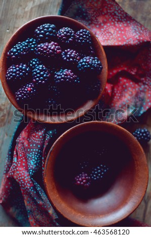 Fresh wild dewberries in a clay bowl on an old  wooden table. Summer berries.