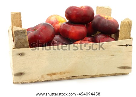 fresh wild flat nectarines in a wooden crate on a white background