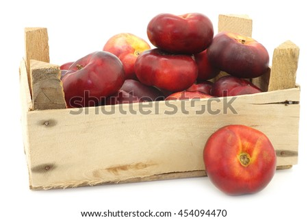fresh wild flat nectarines in a wooden crate on a white background - stock photo