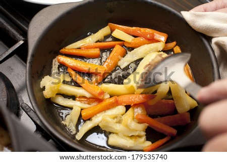 Fresh winter carrot and parsnip batons being sauteed in a metal skillet with a hand holding a spoon above them - stock photo