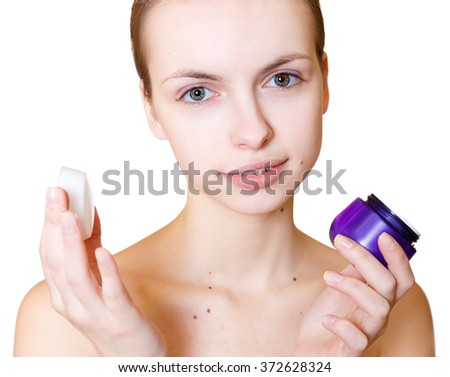 Fresh woman holding container with facial cream and looking at camera