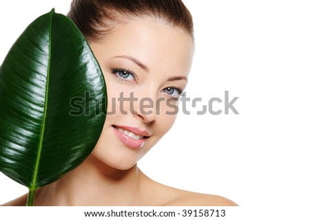 Fresh woman's face with cheerful smile and large green leaf over white background - stock photo