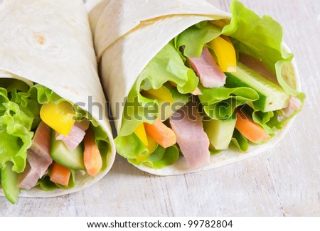 Fresh wrap sandwiches filled with ham, lettuce and pepper - stock photo