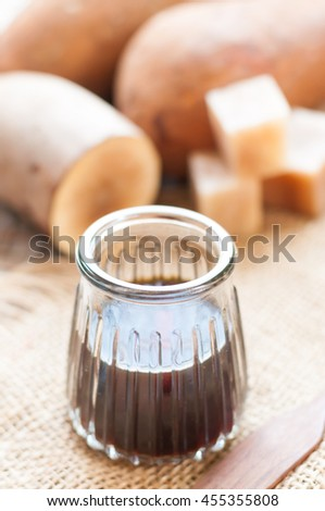Fresh Yacon roots with yacon syrup on wooden board - stock photo