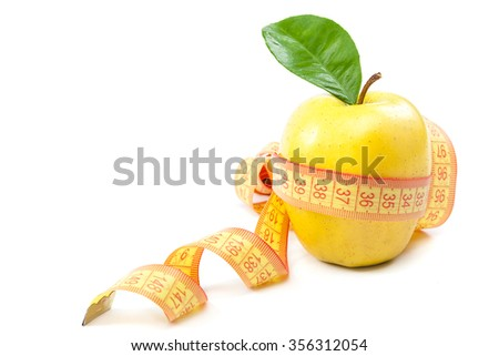 Fresh yellow apple and measuring tape isolated on a white background. - stock photo