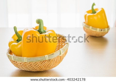 Fresh yellow bell pepper (capsicum) in basket on wood table - stock photo